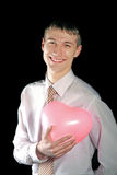 El hombre sostiene un globo rosado del corazón Fotografía de archivo libre de regalías