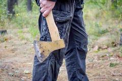 El hombre sostiene un hacha Fotos de archivo
