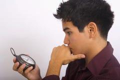 El hombre sostiene un reloj en su mano Imágenes de archivo libres de regalías