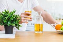 El hombre sostiene un vidrio de zumo de manzana que se sienta en la tabla de cocina foto de archivo
