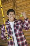 El hombre sostiene una caña de pescar y un cebo foto de archivo