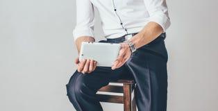 El hombre sostiene una tableta en sus manos en el fondo blanco Él se sienta en una silla vestida en una camisa blanca ostentosa y fotos de archivo