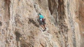 El hombre sube el acantilado con las cuerdas de la seguridad almacen de metraje de vídeo