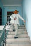 El hombre sube las escaleras con el dolor en el suyo detrás Imagenes de archivo
