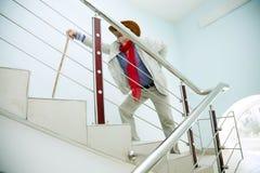 El hombre sube las escaleras con el dolor en el suyo detrás Imágenes de archivo libres de regalías