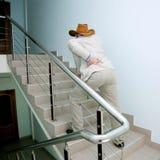 El hombre sube las escaleras con el dolor en el suyo detrás Imagen de archivo