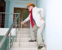 El hombre sube las escaleras con el dolor en el suyo detrás Foto de archivo