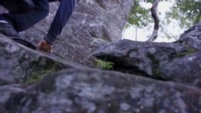 El hombre sube una roca de la proyección cerca de bosque y los apretones se sostienen Atleta en las rocas en el bosque, forma de  Imagen de archivo libre de regalías