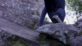 El hombre sube una roca de la proyección cerca de bosque y los apretones se sostienen Atleta en las rocas en el bosque, forma de  Foto de archivo