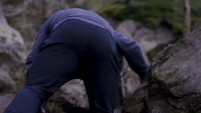 El hombre sube una roca de la proyección cerca de bosque y los apretones se sostienen Atleta en las rocas en el bosque, forma de  Fotos de archivo libres de regalías