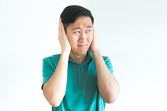 El hombre subrayado que cubre sus oídos y no quiere oír, divulgar demasiado ruidosamente Fotografía de archivo