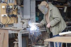 El hombre suelda con autógena piezas del hierro de la soldadura foto de archivo