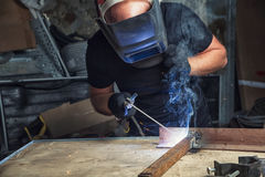 El hombre suelda con autógena una máquina de la soldadura al arco de metal imagenes de archivo