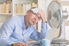 El hombre sufre de calor en la oficina o en casa imagen de archivo libre de regalías