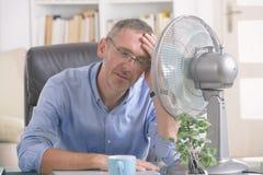 El hombre sufre de calor en la oficina o en casa imagen de archivo