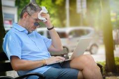 El hombre sufre de calor mientras que trabaja con el ordenador portátil fotos de archivo