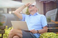 El hombre sufre de calor mientras que trabaja con el ordenador portátil foto de archivo