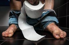 El hombre sufre de diarrea se está sentando en la taza del inodoro fotografía de archivo