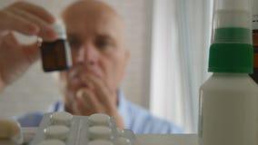 El hombre sufridor elige la medicación para un tratamiento del dolor foto de archivo libre de regalías