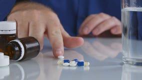 El hombre sufridor que toma medicinas selecciona píldoras de la superficie del vidrio de la tabla fotografía de archivo libre de regalías