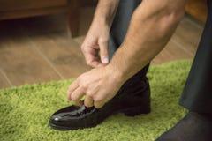 El hombre sujeta los zapatos elegantes imagen de archivo