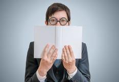 El hombre tímido joven está leyendo y está ocultando su cara detrás del libro Fotografía de archivo libre de regalías