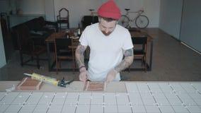 El hombre tatuado aplica las baldosas cerámicas en sistema de la tabla de cocina metrajes