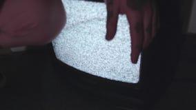 El hombre tatuado los jóvenes se pone en cuclillas en piso con el trabajo de TV estática, pantalla táctil almacen de metraje de vídeo