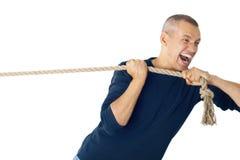 El hombre tira de una cuerda Foto de archivo libre de regalías