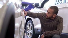 El hombre toca el ala del coche en la representación almacen de video