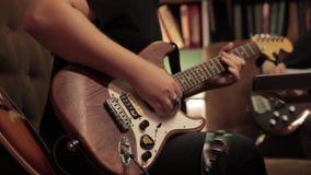 El hombre toca una guitarra eléctrica marrón-blanca dentro mientras que se sienta en un sofá almacen de metraje de vídeo
