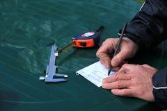 El hombre tomó medidas y dibuja el esquema de su idea en el shee de papel Fotografía de archivo