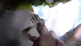 El hombre toma a ducha de aire abierto cerca la piscina en las zonas tropicales metrajes