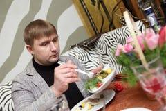 El hombre toma el aperitivo Imagen de archivo