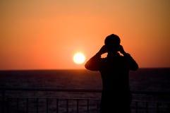 El hombre toma la imagen de la puesta del sol Fotos de archivo libres de regalías