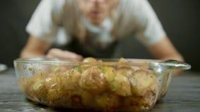 El hombre toma la patata cocida de oro del plato de los vidrios metrajes