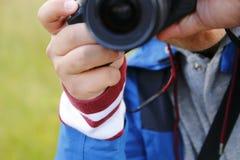 El hombre toma las fotos con una cámara refleja reflectora al aire libre en naturaleza Foto de archivo