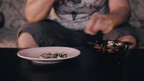 El hombre toma las semillas de la situación de la taza en la tabla y las limpia de la cáscara El hombre lanza la cáscara en una p metrajes