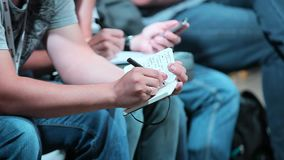 El hombre toma notas en un cuaderno en la conferencia almacen de metraje de vídeo