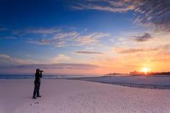 El hombre toma una fotografía de la salida del sol imagenes de archivo