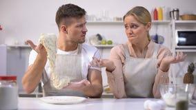 El hombre torpe que estira la pasta, mirando a la esposa, los pares tiene dificultad que hace la torta almacen de metraje de vídeo