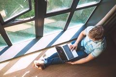 El hombre trabaja con el ordenador portátil que se sienta en el piso cerca de la ventana abierta Imagen de archivo