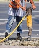 El hombre trabaja con un martillo de aire Imagenes de archivo