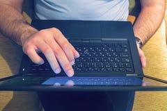 El hombre trabaja con un ordenador portátil que toca la pantalla con sus fingeres fotografía de archivo libre de regalías