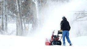 El hombre trabaja con un ventilador de nieve para quitar nieve nuevamente caida de la calzada imagen de archivo