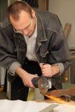 El hombre trabaja con una sierra de la circulación en estudio Fotos de archivo libres de regalías