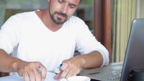 El hombre trabaja de hogar en el ordenador portátil Concepto del trabajo almacen de metraje de vídeo