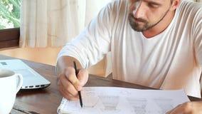 El hombre trabaja de hogar en el ordenador portátil Concepto del trabajo metrajes