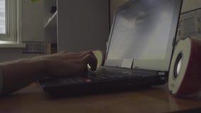 El hombre trabaja detrás del ordenador portátil