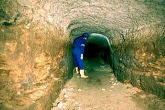 El hombre trabaja en el túnel largo antiguo místico de las paredes anaranjadas de la piedra arenisca, ciudad subterráneo Fotos de archivo libres de regalías